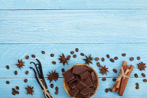 chocolate, vanilla sticks, cinnamon, coffee beans on blue wooden background with copy space for your text. Top view