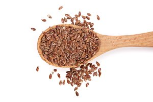 Flax seeds in a wooden spoon isolated on white background. Top view
