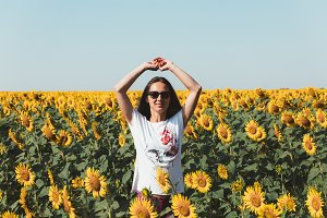 Young beautiful girl in sunglasses stands in field with sunflowers with arms raised and looks forward