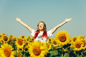 Beautiful young girl with red hair standing in a field with sunflowers with full hands and smiling