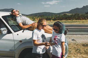 Three friends are resting during a car trip. The guy lies on the hood of the car and drinks tea, two girls stand near the car and learn the route in the smartphone's navigator