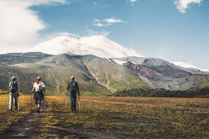 A team of travelers with backpacks and trekking sticks goes towards the mountain range and Mount Elbrus, a back view