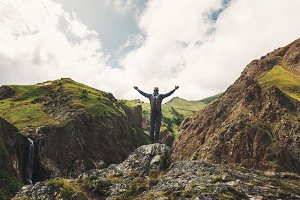 A young male traveler stands on top of a mountain with his hands up and enjoys the view of the summer mountains