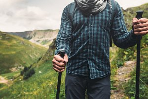 Man with hiking equipment walking  on mountains background