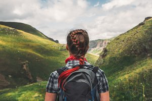 unrecognizable young girl with red hair and a backpack is enjoying the view of the summer mountains, the back view