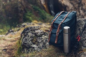 A close-up, a blue hiking backpack, a thermos and trekking sticks lie near the cliff