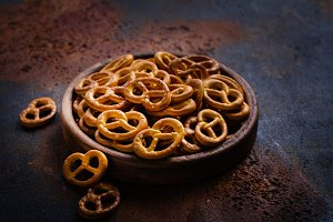 Heap of mini pretzels on wooden plate
