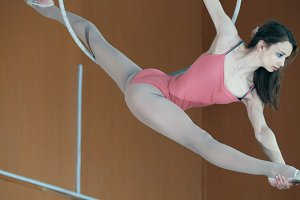 Young girl acrobat shows flexibility on gymnastic hoop