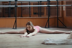 Beautiful gymnast does the splits in a room with ballet lathe and mirrors