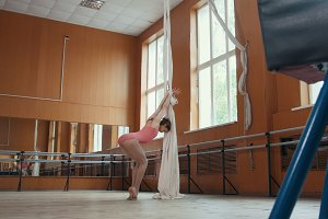 Beautiful flexible girl warming up at the ballet bar