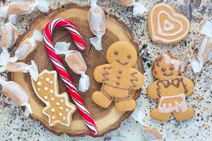 Christmas gingerbread cookies and caramel candies on wooden board, horizontal, top view