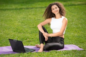 Sporty young woman sitting on the grass with laptop