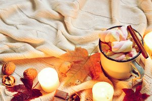 Toned Autumn banner made of dried fall leaves, mug of cocoa with marshmellows, nuts, cinnamon, candles on beige plaid