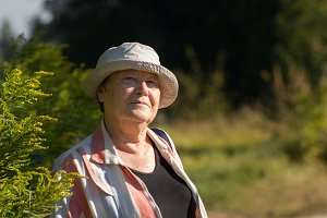 Old senior happy woman smiling in the paek or garden