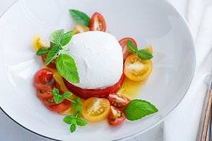 Caprese salad with red and yellow tomatoes, mozarella, basil and olive oil. Close view. White background.