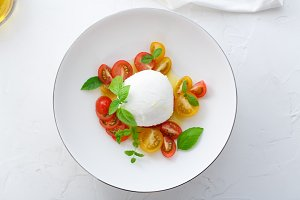 Caprese salad with red and yellow tomatoes, mozarella, basil and olive oil. Close view. White background top view