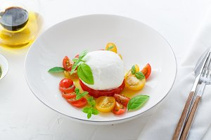 Italian appetizer caprese salad with ripe red and yellow cherry tomatoes, mozarella, fresh basil leaves and olive oil. White background.