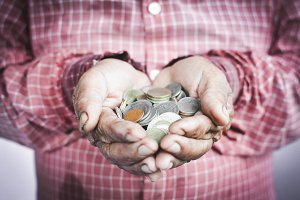 Old hands holding coins