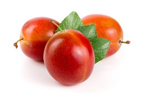 red plums with leaves isolated on white background