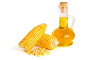 Corn oil in decanter, fresh corn cobs and grains isolated on white background