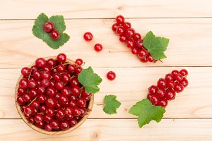 Red currant berries in a wooden bowl with leaf on the light wooden background. Top view