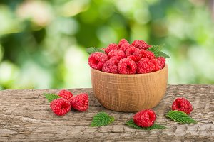 Raspberry in a wooden bowl on table with a blurry garden background