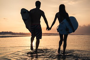 Couple of surfers -man amd woman - walking at the beach at sunset
