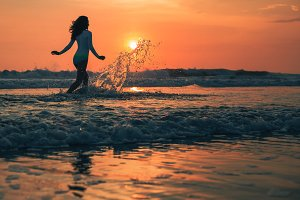 Silhouette of the woman running in the water during sunset.