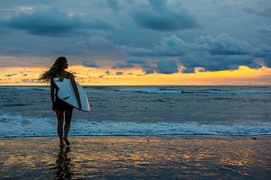 Female surfer with board in hands walking along coastline on sandy beach over sunset