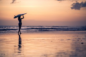 Silhouette of female surfer with board in hands walking along coastline on sandy beach over sunset