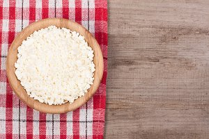 Cottage cheese in a wooden bowl on old wooden background with copy space for your text. Top view