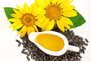 Sunflower oil, seeds and flower isolated on white background. Top view