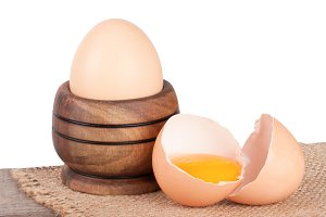 Broken egg with yolk and eggshell on a wooden table with a white background