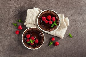 Chocolate dessert with fresh raspberries on dark stone backgroun
