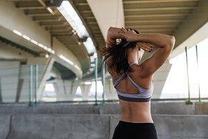 Woman in sport bra under a bridge