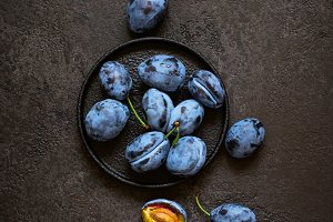 Dark blue plums in cast iron plate on black background
