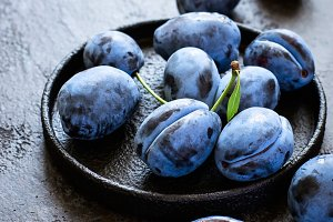Dark blue plums in cast iron plate on black background closeup