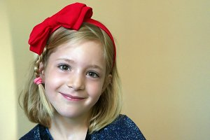 Portrait of a little blonde girl with a red bow on his head