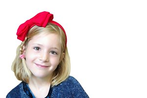 Portrait of a little girl with a red bow on his head