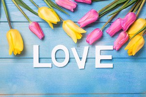 Word love and bright tulips flowers