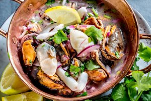 Peruvian Latin American seafood shellfish ceviche cebiche. Raw seafoods - mussels, shrimps, clams, squides marinated in lemon juice with red onion and coriander in cooper bowl, gray slate background
