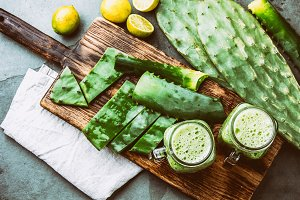 Healthy cactus nopales, aloe vera and lemon detox drink in jars and ingredients on gray background. Top view