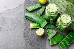 Healthy cactus nopales, aloe vera and lemon detox drink in jars and ingredients on gray background. Top view