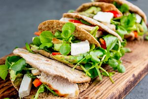 Pita sandwiches stuffed with chicken, vegetables and cheese on wooden cutting board