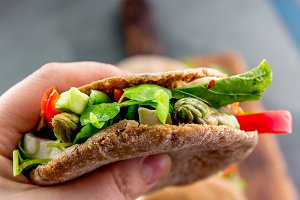 Hand holding vegetarian pita sandwich stuffed with asparagus, bell pepper, avocado and fresh leaves