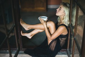 Young beautiful blonde woman with a cup of hot drink in her hands in a window, the girl is emotionally relaxed and happy
