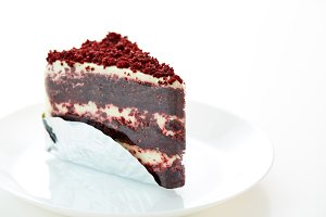 piece of delicious Red Velvet cheesecake on white