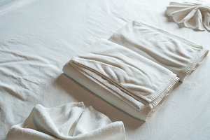 White bath towel on bed.