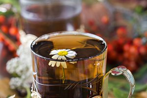 glass of hot tea with autumn leaves