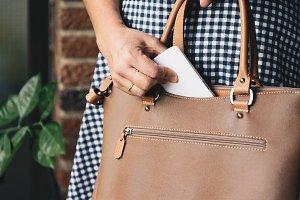 Closeup photo of stylish woman taking cellphone out of handbag.
